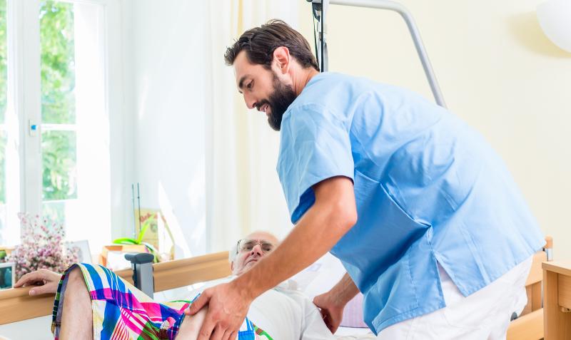Foto eines Pflegers, der einen Bewohner beim Hinlegen unterstützt.